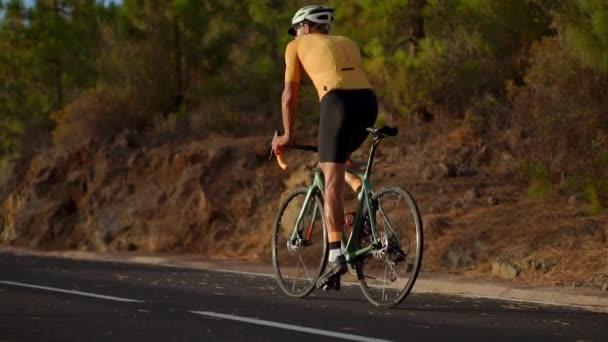 Profesionální cyklista v helmě a sportovní vybavení jezdí na horské silnici