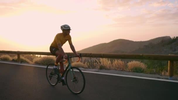 Profesionální cyklista v helmě a sportovní vybavení jezdí na horské silnici při západu slunce ve zpomaleném filmu. Steadicam