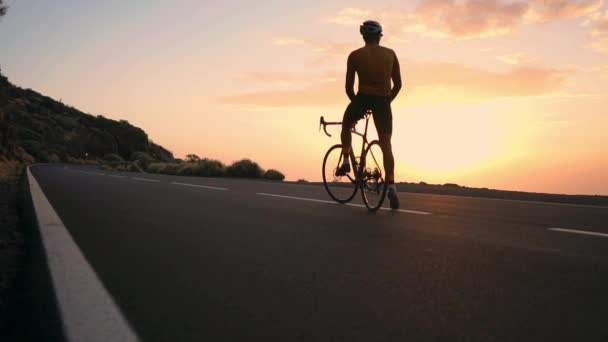 Muž cyklista v žluté tričko v horách sledovat západ slunce. Odpočinek po cvičení, Železný muž