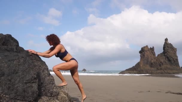 A woman performs squats and lunges from a rock on a beach near the ocean