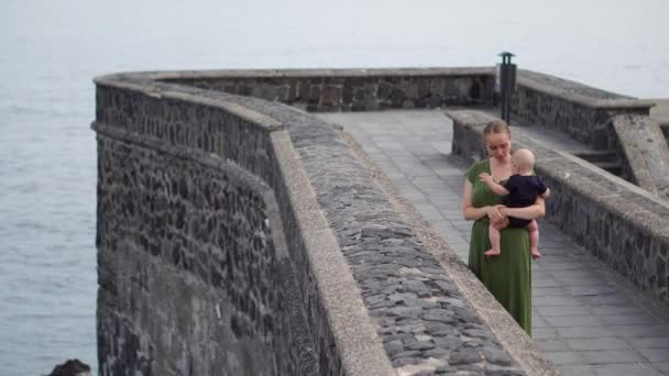 Young mother plays with her son baby on the waterfront near the ocean on the ancient square of Europe.