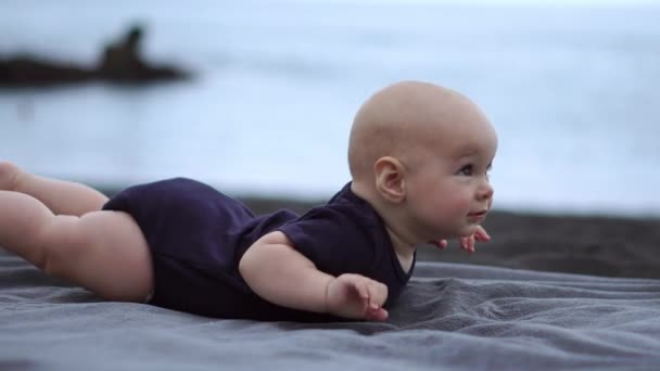 The baby lies on his stomach on the black sand near the ocean and laughs looking at the camera