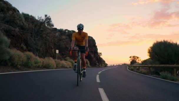 Mladý sportovní muž jede kolo na horských serpentin a dívá na kameru v žluté tričko a sportovní vybavení. Zpomalený pohyb steadicam