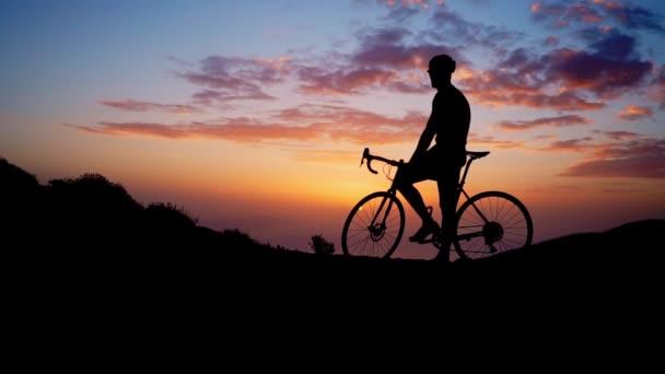 Mladý sportovní muže, který seděl na kole na vrcholu hory v žluté tričko helmu a sportovní vybavení, při pohledu na západ slunce. Zpomalený pohyb steadicam