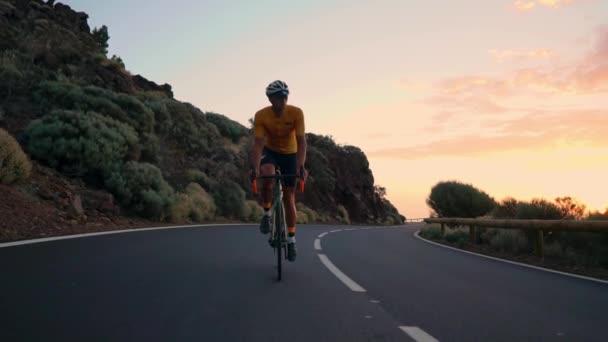 Mladý sportovní muž jede kolo na horských serpentin v žluté tričko helmu a sportovní zařízení na kameru při pohledu na západ slunce. Zpomalený pohyb steadicam