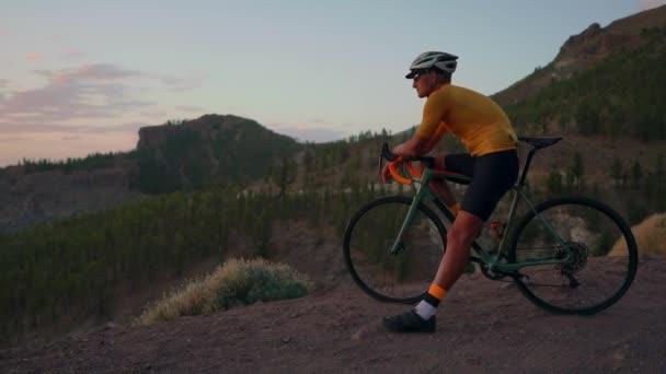 Mladý sportovní muže, který seděl na kole na vrcholu hory v žluté helmě tričko a sportovní vybavení při pohledu na krásný výhled na hory a zapadající slunce. Zbytek po tréninku. Pomalu