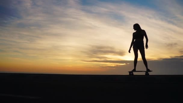 Silueta dívky v šortkách a tenisky Skateboarding po silnici proti oceán a hory.