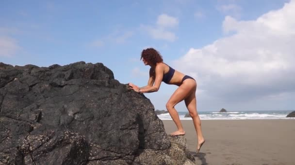 The slender woman on the beach with volcanic sand sports in a very beautiful place