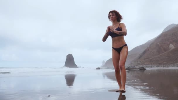 A slender woman near the ocean walking on the water sports to performing lunges on each leg. Exercises for thigh muscles in slow motion