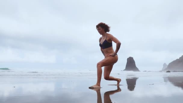 Along the ocean, a woman goes in for sports performing lunges in turn on each leg against the background of rocks and water