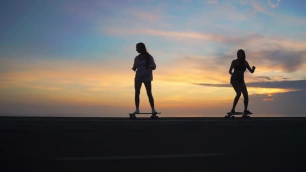 Skateboarding silhouette of two girls against the sky and the sun