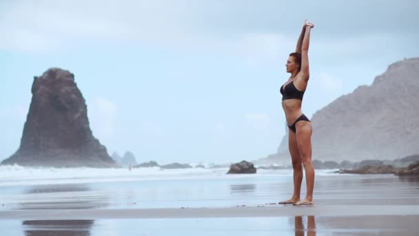 A beautiful woman on the ocean beach with black volcanic sand performs gymnastic exercises practicing a healthy lifestyle and outdoor training. Fitness training