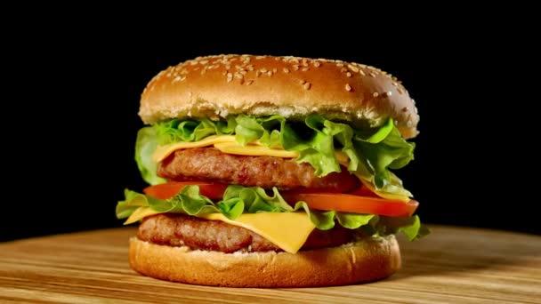 Čerstvé chutný hamburger otočení na černém pozadí. Bezproblémová loopable záběr, 4k.