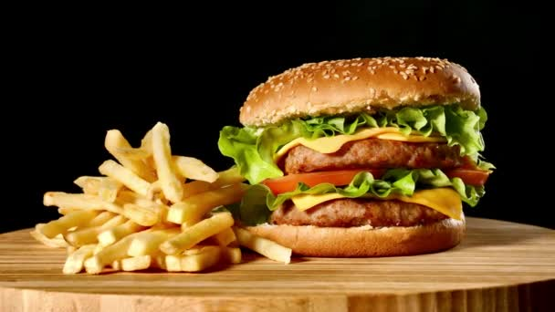 Řemeslo hovězí burger a hranolky, omáčka izolované na černém pozadí. Rychlé občerstvení