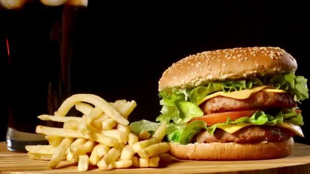 hamburger s hranolky a sklenici s ledem cola na černém pozadí rustikální