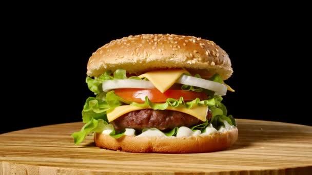 Cheesburger se slaninou na tmavém pozadí. Detail. Makro fotografování