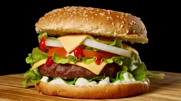 Velký Burger s hovězí kotleta, rajčaty, žampiony a okurky s rozpečeným sýrem se otočí na dřevěné desce na černém pozadí.