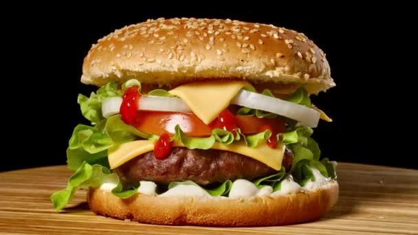 große Burger mit Rinderschnitzel, Tomaten, Pilzen und Gurken mit geschmolzenem Käse dreht sich auf einem Holzbrett auf schwarzem Hintergrund.