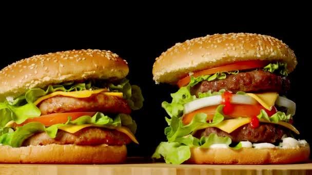 Pojem Americká Rychlé občerstvení. Šťavnaté americký hamburger s dvěma hovězí kotlety, s omáčkou a ogretsami na černém pozadí. Kopírovat prostor
