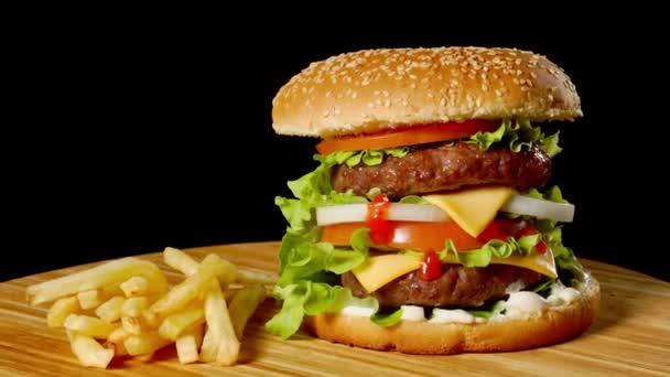 Řemeslo hovězí burger a hranolky na dřevěný stůl izolované na černém pozadí.