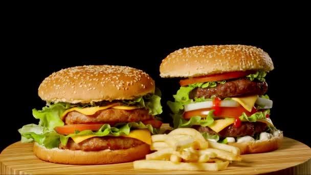 Dvě plavidla hovězí hamburgery na dřevěný stůl izolované na pozadí tmavé odstíny šedi.
