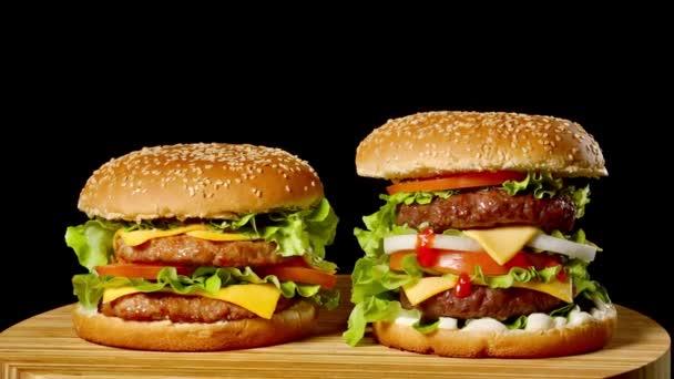 Detail ze dvou chutné hamburgery s housky sezamové otočení na černém pozadí, rychlého občerstvení bezešvé smyčka shot .