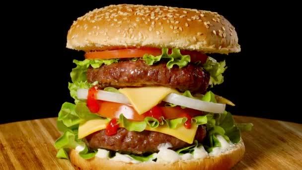 Cheesburger se slaninou na tmavém pozadí. Detail. Makro fotografování.