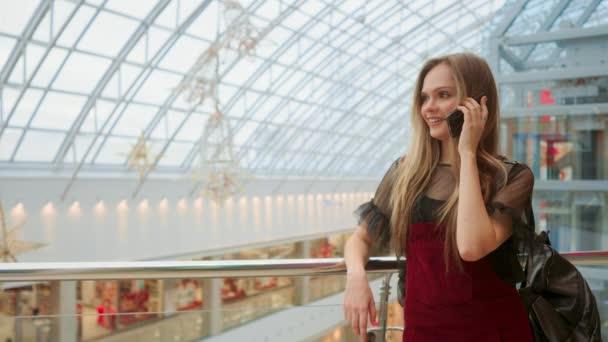 Prodej, konzumerismus: mladá žena s chytrými telefony a nákupní tašky, stojí a mluví poblíž nákupního centra
