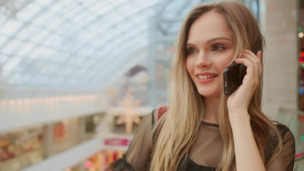 krásná dívka mluví na smartphone a sedí s nákupní tašky v obchoďáku