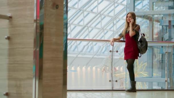 Értékesítés, fogyasztás: fiatal nő, okostelefonok és a bevásárló szatyrok állt, és beszélt közelében bevásárlóközpont