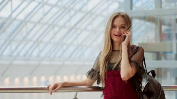 Gyönyörű lány beszél egy mozgatható telefon néz a kamerába, és mosolyog. gyönyörű lány a smartphone beszélő, és ül a Mall bevásárló szatyrok