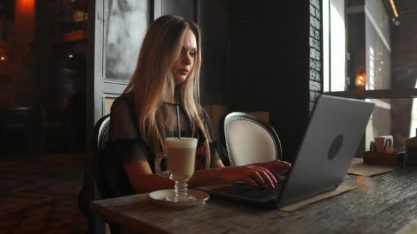 Portrait of a young girl she works as a freelancer in a cafe drinking a delicious hot Cup of coffee from text send mail
