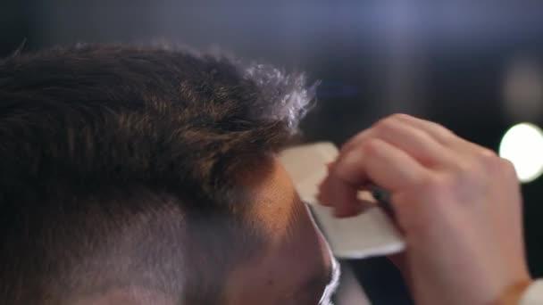 Holič, sušení mužských vlasů v kadeřnictví. Zblízka kadeřník foukat vlasy člověka se sušičkou v holičství. Samec hairstylish dělá účes v beauty studio