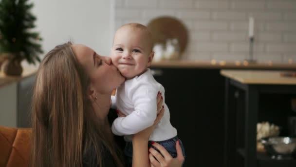Maminka drží dítě a dětské úsměvy při pohledu na svou milovanou matku. Společně se stát v bílé kuchyni na Štědrý den na pozadí věnce a vánoční stromky. Šťastný matka a dítě