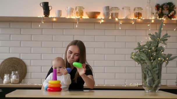 Batole s mámou hrát s hračkami v dětském pokoji pokoji. Matka se jí 1-letý chlapeček baví doma
