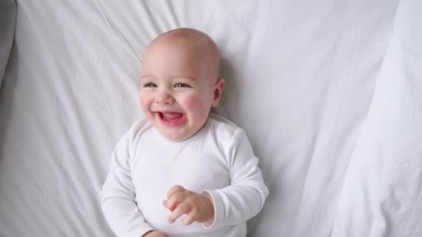Dítě v bílé tričko leží na bílé posteli, při pohledu na fotoaparát a se smíchem v pomalém pohybu, pohled shora