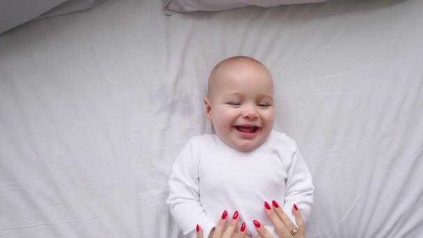 Novorozené dítě leží na posteli, při pohledu do kamery a okolí na bílé prostěradlo, pohled shora. Dítě ví, svět, pohled shora