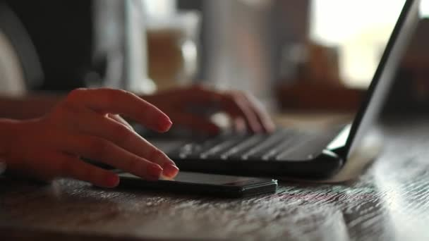 Detail zadní pohled mladých obchodních žena pracující v kanceláři interiéru na pc držte smartphone a díval se na obrazovky s diagramy. Úřadu osoba, která používá mobilní telefon a notebook