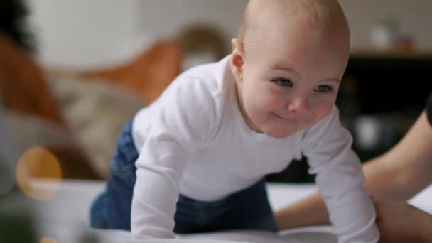 Fiatal anya és újszülött gyermeke átölelve. Anya a szoptatott baba. Nő és az újszülött fiú pihenjen egy fehér hálószoba. Családi otthon. Szeretet, a bizalom és a gyengédség koncepció. Ágynemű és textil gyerekszobába.
