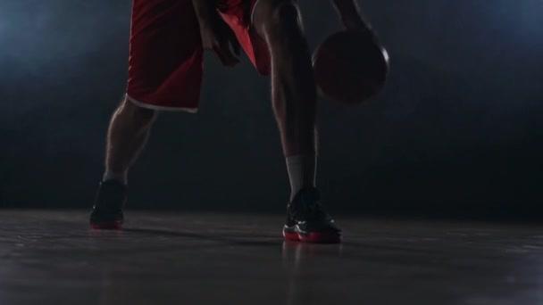 männlicher Athlet in Sportbekleidung und Turnschuhen prokipyvaet Basketballball zwischen den Beinen auf dem Basketballfeld in den Rauch in Zeitlupe