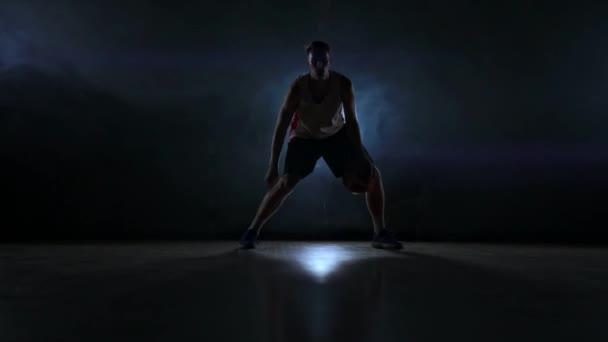 Dovednost driblování basketbalista potmě na košíkovou s podsvícením v kouři. Zpomalený pohyb streetball
