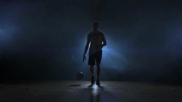 Basketbalový hráč jde rovnou do kamery v temné místnosti s podsvícením zpět v kouři, při pohledu na fotoaparát ve zpomaleném filmu. Steadicam