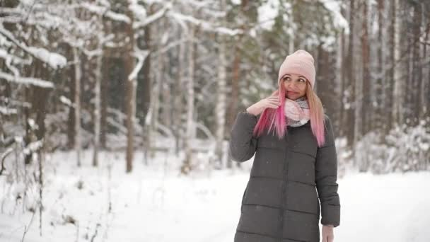 glückliche schöne Frau in lässigem Stil, die mit den Händen nach oben rollt, während es im Winter auf dem schönen Stadtplatz schneit. Draußen. Porträtaufnahme