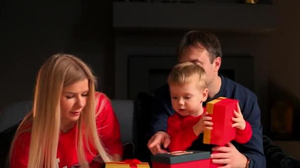 Familie Mama Papa und Sohn an Weihnachten offene Geschenke zu Hause sitzen auf der Couch im weihnachtlichen Interieur. warme und gemütliche Atmosphäre zu Hause