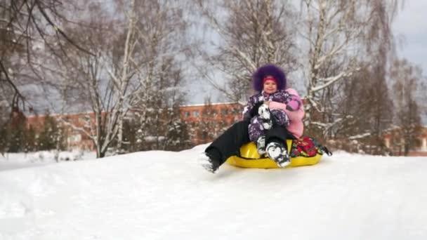 Glückliche Mutter und Tochter rodeln im Winter im Schnee und spielen Schneebälle. Mutter und Kind lachen und jubeln, gleiten auf einem aufblasbaren Schlauch. Familienspielpark in den Weihnachtsferien. Zeitlupe