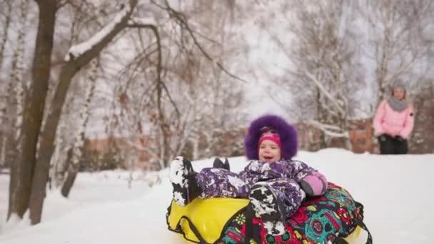 Šťastná Maminka a dcera, sáňkování v zimě ve sněhu a hrající sněhové koule. matka a dítě se smát a radovat skluz na nafukovací trubice. Rodina hrát parku během vánočních svátků. Zpomalený pohyb