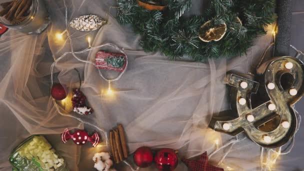 Kreativního koníčka. Dárkové balení. Balení moderní vánoční dárek pole v elegantní šedé papír s saténovou červenou stuhou. Pohled shora rukou na bílé dřevo stůl s větve stromů jedle, dekorace