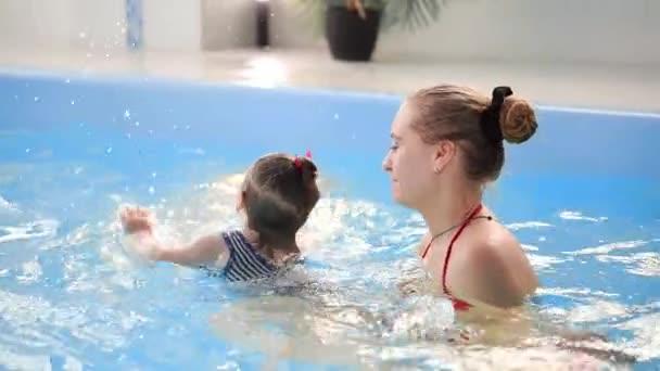 Aranyos baba fiú élvezi az anyjával, a medencében.