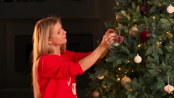 Kezét a nő díszítő karácsonyfa a Karácsony fények fénye.