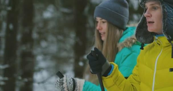 Muž v žlutá saka a žena v modré kombinéze v zimě v lese lyžování v pomalém pohybu